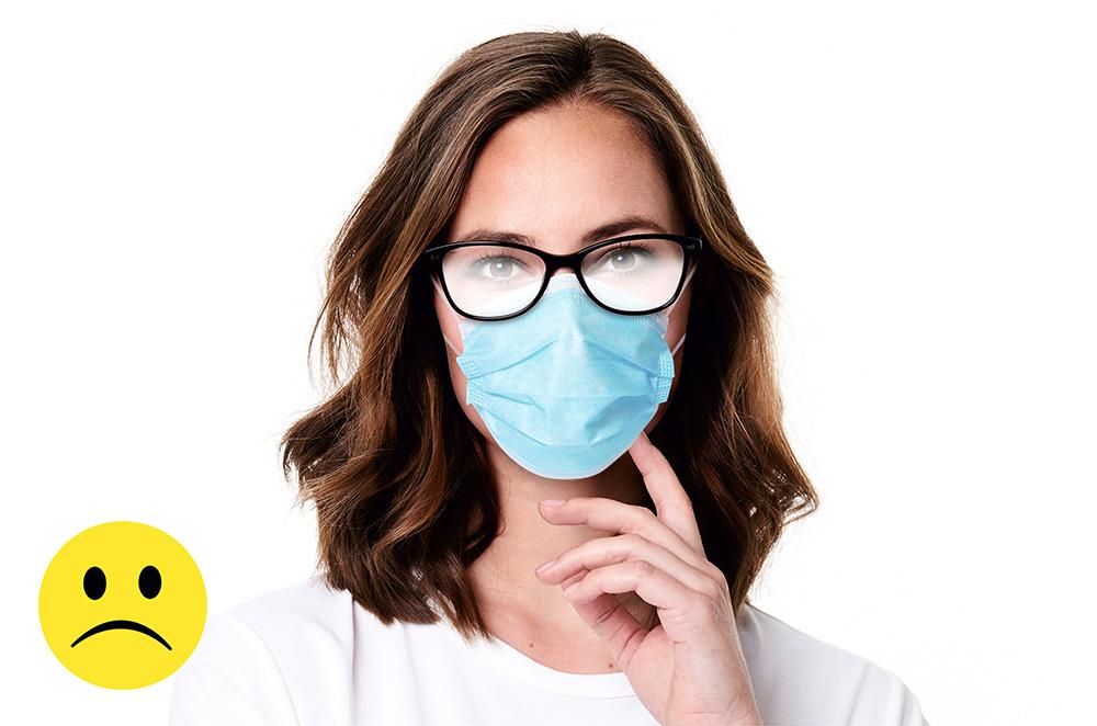 Junge Frau mit Mund & Nasenmaske und beschlagener Brille